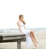Attractive young woman sitting at the beach Stock Photo