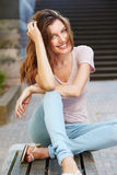 Attractive young woman sitting on bench outdoors Stock Photography