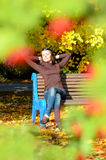 Attractive young woman sitting on brown wooden bench with hands behind her head in beautiful park. She closed eyes Royalty Free Stock Image
