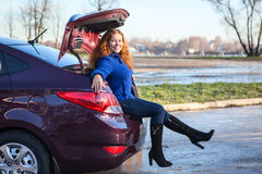 Vehicle luggage trunk with sitting woman inside. Attractive young woman sitting in car luggage trunk Stock Images