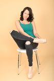 Attractive Young Woman Sitting on a Chair in High Heel Shoes Adjusting Her Shoes Stock Photos