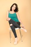 Attractive Young Woman Sitting on a Chair in High Heel Shoes and Royalty Free Stock Photography