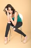 Attractive Young Woman Sitting on a Chair in High Heel Shoes and Royalty Free Stock Image