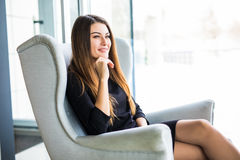 Attractive young woman sitting on a chair while working in a cafe. Attractive young woman sitting on a chair in a cafe Royalty Free Stock Images