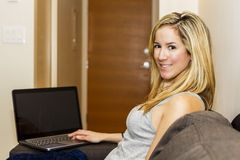 Attractive Young Woman Sitting On Couch With Laptop Computer Stock Photos