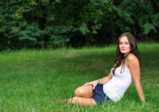 Attractive young woman sitting in field Stock Image