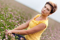 Attractive young woman sitting in field surrounded by wildflowers. Attractive young woman sitting alone in field surrounded by wildflowers on summer day Stock Image