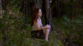 Attractive young woman sitting in the forest alone. She is doing her hair up and looks down. Slow motion stock video footage