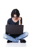 Attractive young woman sitting in front of a laptop. Royalty Free Stock Photos