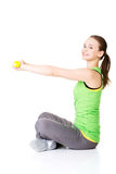 Attractive young woman sitting and holding free weights. Royalty Free Stock Image
