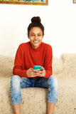 Attractive young woman sitting at home with mobile phone. Portrait of an attractive young woman sitting at home with mobile phone Royalty Free Stock Image