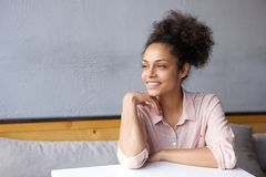 Attractive young woman sitting indoors smiling Royalty Free Stock Photography