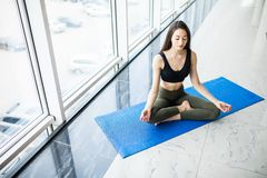 Attractive young woman sitting on lotus position on floor with eyes closed. Royalty Free Stock Image