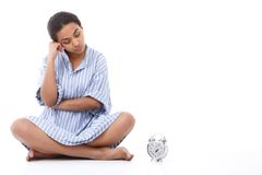 Attractive young woman sitting near alarm clock Royalty Free Stock Photo