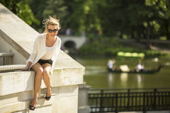 An attractive young  woman sitting near the water reservoir in the city Park. Stock Photo