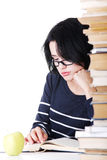 Attractive  young woman sitting next to stack of book with an app Stock Photo