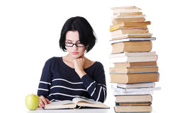 Attractive young woman sitting next to stack of book with an app Royalty Free Stock Image