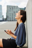 Attractive young woman sitting outdoors with cell phone and laughing Royalty Free Stock Images