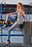 Attractive young woman sitting on pier enjoying spring warm weather. Stock Photography