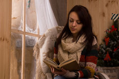 Attractive young woman sitting reading Royalty Free Stock Image