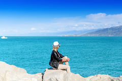 Attractive young woman sitting on rock Royalty Free Stock Images