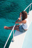 Attractive young woman sitting on shipboard. Pretty young woman sitting on shipboard with legs out Stock Images