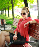 Attractive young woman sitting in a summer park Royalty Free Stock Images