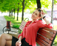 Attractive young woman, sitting in a summer park Stock Image