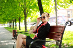 Attractive young woman sitting in a summer park Stock Photo