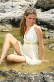 Attractive young woman sitting in the water Stock Images