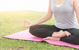 Attractive young woman sitting in yoga lotus position Royalty Free Stock Image