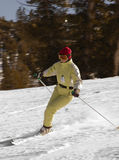 Attractive young woman skiing. A young woman is skiing at a ski resort at lake Tahoe, California. Background is motion blurred Stock Photography