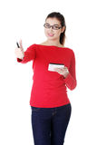 Attractive young woman skowing OK, standing with pen and paper. Royalty Free Stock Photos
