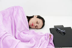 Attractive young woman sleeping in bed with laptop. Photo of the Attractive young woman sleeping in bed with laptop Royalty Free Stock Photography
