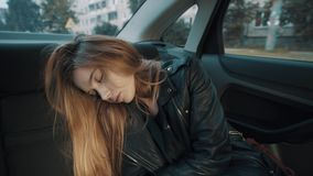 Attractive young woman sleeping on car backseat moving along city street stock video