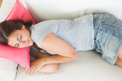 Attractive young woman sleeping on her white couch Royalty Free Stock Photo