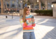 Attractive young woman on smart phone checking social media mobile apps outside city stock images