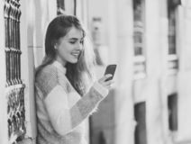 Attractive young woman on smart phone checking social media mobile apps outside city stock image