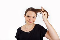 Attractive young woman smiles and plays with her hair Royalty Free Stock Photos