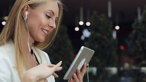 Attractive young woman smiles working with a tablet in the earphones stock video footage
