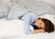 Attractive young woman smiling in bed Royalty Free Stock Image