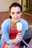 Attractive young woman smiling and eating ice cream outside Stock Photography