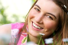 Attractive young woman smiling with flower outdoors Stock Images