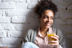 Attractive young woman smiling with glass of fruit juice Stock Images