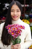 Attractive young woman smiling and holding flowers Royalty Free Stock Images