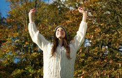 Attractive young woman smiling outdoors with arms outstretched Stock Photos