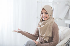 Attractive young woman smiling presenting to copy space. Portrait of attractive young woman with hijab smiling presenting to copy space Stock Image
