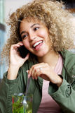 Attractive young woman smiling and talking on cellphone Stock Image