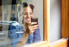 Attractive young woman smiling and using mobile phone Royalty Free Stock Photo