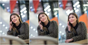 Attractive young woman speaking on mobile in mall. Beautiful fashionable girl in dark gray fluffy jacket posing in modern mall Royalty Free Stock Photo